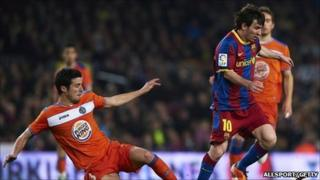 Lionel Messi (R) of Barcelona is tackled by Ivan Marcano of Getafe during the La Liga match between Barcelona and Getafe at Camp Nou on March 19, 2011 in Barcelona
