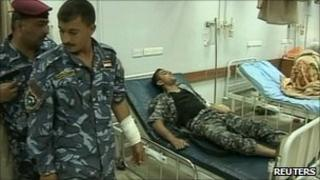 Injured policeman in a Baghdad hospital after an attack on the Sacred Heart church (24 April 2011)