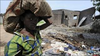 A child carries a bag as she walks past a burnt house in the town of Duekoue where a mass grave was found (17 April 2011)