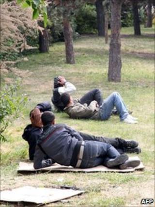Tunisian migrants lie on grass in a park near the Porte de la Villette, northern Paris, 27 April