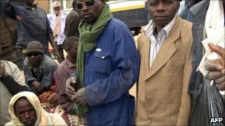 African nationals, mainly Nigerians, wait at a bus depot in Agadez on 22 Marc 2011 after feeing conflict in Libya