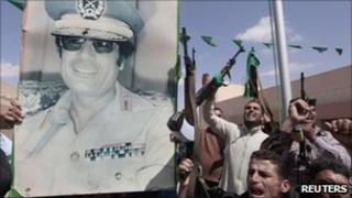 Libyan soldiers hold a poster of Col Muammar Gaddafi - 27 April 2011