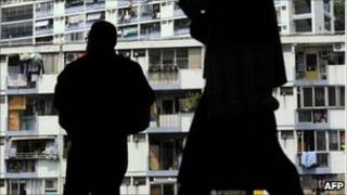 Workers silhouetted against a public housing estate in Hong Kong
