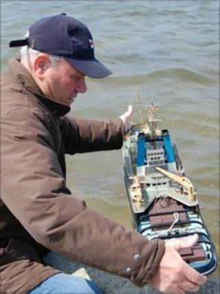 Les Barnes putting a model boat in Guernsey's model yacht pond