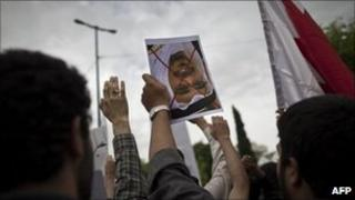 "An Iranian student holds upside down a portrait of Bahrain's King Hamad bin Issa al-Khalifa with a red ""X"" drawn across it during a protest outside the Bahrain embassy in Tehran on 30 April 2011"