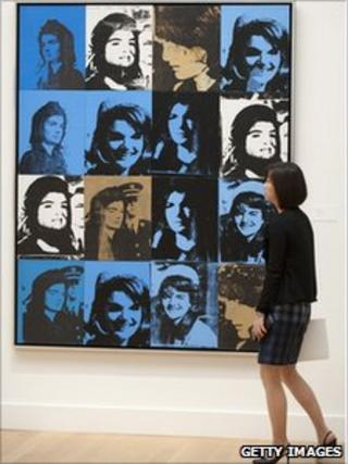 A woman views Andy Warhol's Sixteen Jackies
