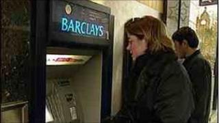 woman using Barclay's cash machine