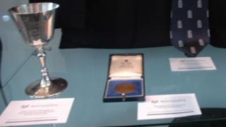 The silver goblet to the left and the display card in front of it which were taken