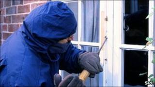 Posed image of burglar breaking into a house