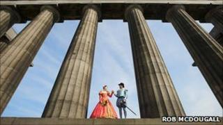 A man and a woman dressed in Tudor clothes stand together between columns
