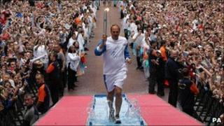 Sir Steve Redgrave carrying the Olympic torch along Pall Mall in 2008