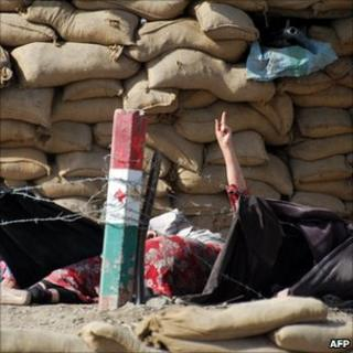 A wounded woman raises her hand next to a security checkpoint during exchange of fire with Pakistani troops in Quetta on 17 May 2011.
