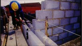 Builder using plumb line on wall