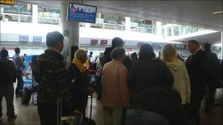 People queue with luggage