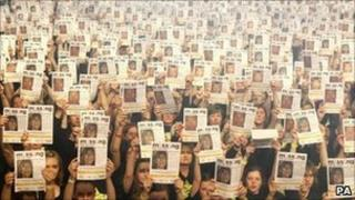 10,000 members of the Rock Choir hold up posters showing pictures of missing children, at Wembley Arena