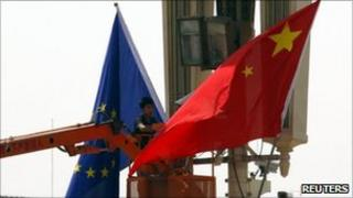 A worker hangs an EU flag next to a Chinese national flag at Beijing's Tiananmen Square