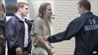 Brian David Mitchell being escorted by two police officers into the Salt Lake City courthouse on Wednesday