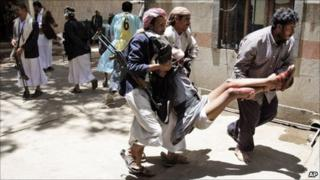 Tribesmen carry an injured colleague during clashes with Yemeni security forces in Sanaa, Yemen, on 24/5/11
