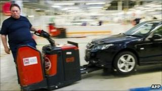 A Saab worker takes a car from the production line on 27 May