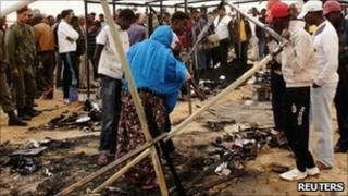 Refugees gather around a burnt tent on 23 May 2011 at a refugee camp in Choucha, Tunisia