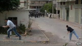 Unverified image appearing to show men throwing stones at security forces in Baniyas, Syria