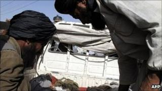 Two Afghan men look down at the bodies of two children (not pictured), said to have been killed in a Nato air strike, at a hospital in Lashkar Gah in Helmand province on 29 May 2011