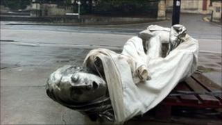 One of the three figures smashed on the pavement