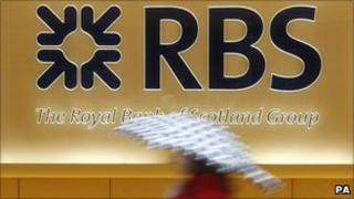 Woman walks past an RBS sign