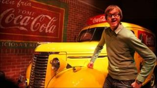 Alex Riley in front of an old Coca-Cola car