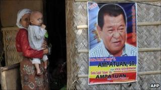 An elderly woman carrying a child stands beside a campaign poster of Andal Ampatuan Snr in Maguindanao, southern Philippines on May 8, 2010