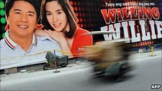 """This photo taken on April 9, 2011 shows a vehicle speeding past a Manila billboard advertising Philippine television game show """"Willing Willie"""" and its host Willie Revillame (L) and co-host Shalani Soledad"""