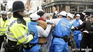 Police and Chinese security officers tackle a protester during the London leg of the Beijing torch relay