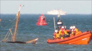 RNLI crew trying to save sinking yacht