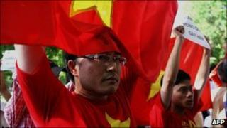 Protesters hold Vietnamese flags and anti-China banners during a protest in Hanoi