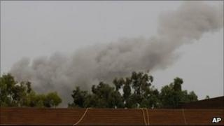 A smoke plume rises into the sky over Tripoli, Libya, following an air strike.