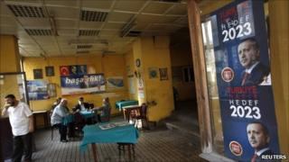 Men sit in a tea house in Istanbul with Prime Minister Tayyip Erdogan's election campaign posters on the window, 9 June