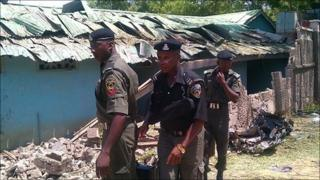 Police officers inspect the remains of St Patrick's church in Maiduguri