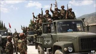 Syrian soldiers stand inside lorries near the town of Jisr al-Shughour (11 June 2011)