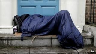 A man asleep in a doorway