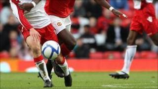 Fotballers chasing ball