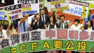 A group of legislators from Taiwan's anti-Beijing opposition Democratic Progressive Party hold protest signs on the legislative floor on August 17, 2010