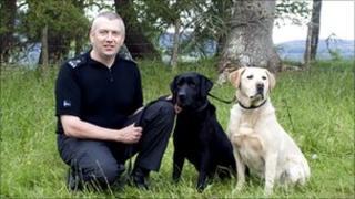Special Constable Michael Coutts with Buzz (black Labrador) and Nico (golden Labrador)
