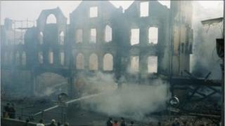 Firemen damp down shops destroyed by a firebomb in Armagh, County Armagh
