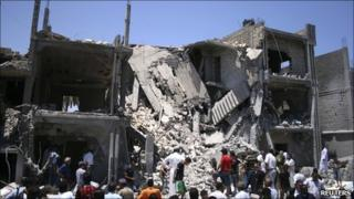 People inspect the rubble of a residential building, which Libyan officials say was hit by a Nato air strike in Tripoli's Souq al-Juma district on 19 June 2011