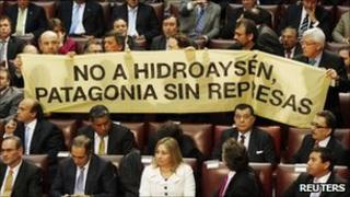 """Opposition deputies hold up a placard in protest against the dam during Chile""""s President Sebastian Pinera's annual address at the national congress building in Valparaiso city on 21 May, 2011"""