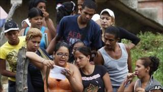 A relative of an inmate reads a list of prisoners who survived outside El Rodeo I prison in Guatire, Venezuela, Monday, 20 June 20
