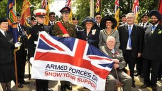John Sheppard is sitting holding the Armed Forces flag