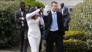 Abiola Abdul Kareem behind woman in white