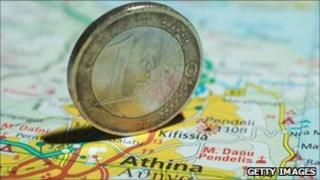 A euro coin on a map of Greece
