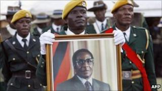 Zimbabwean soldiers hold a picture of President Robert Mugabe sworn in for a sixth term in office in Harare, on 29 June 2008 after being declared the winner of a one-man election